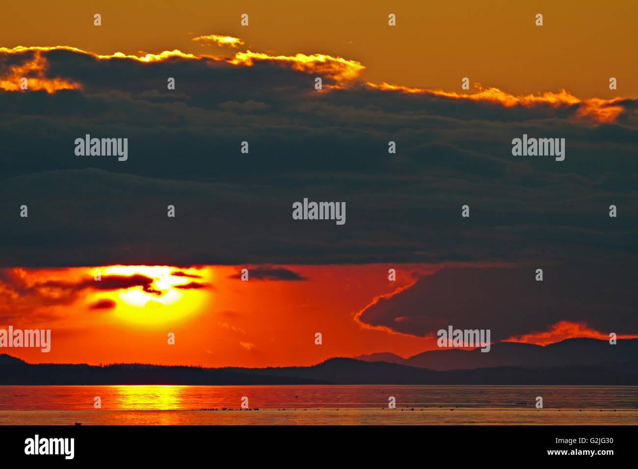 Atardecer con nubosidad Cormorant Island y el norte de la isla de Vancouver, British Columbia, Canadá. Imagen De Stock