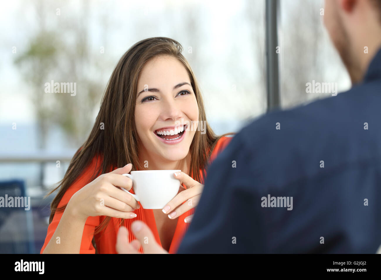 Feliz mujer dating en un café mirando a su pareja y sosteniendo una taza Imagen De Stock