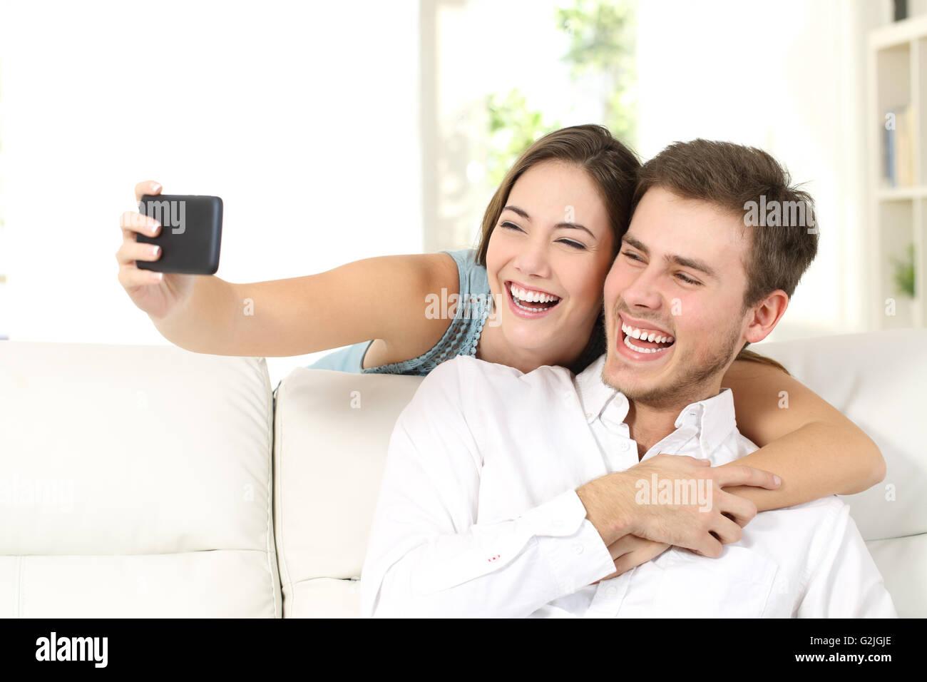 El matrimonio o una pareja riendo y tomando un selfie con teléfono sentados en un sofá en casa Imagen De Stock