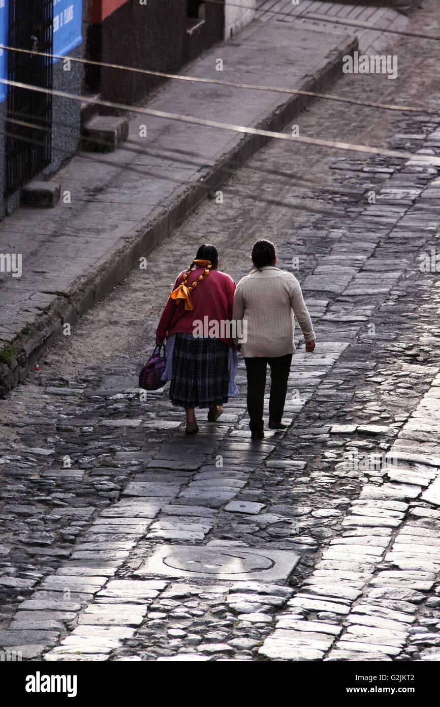 Una madre y abuela guatemaltecos mayas caminando por una calle adoquinada reflectante húmedo en Quetzaltenango Imagen De Stock