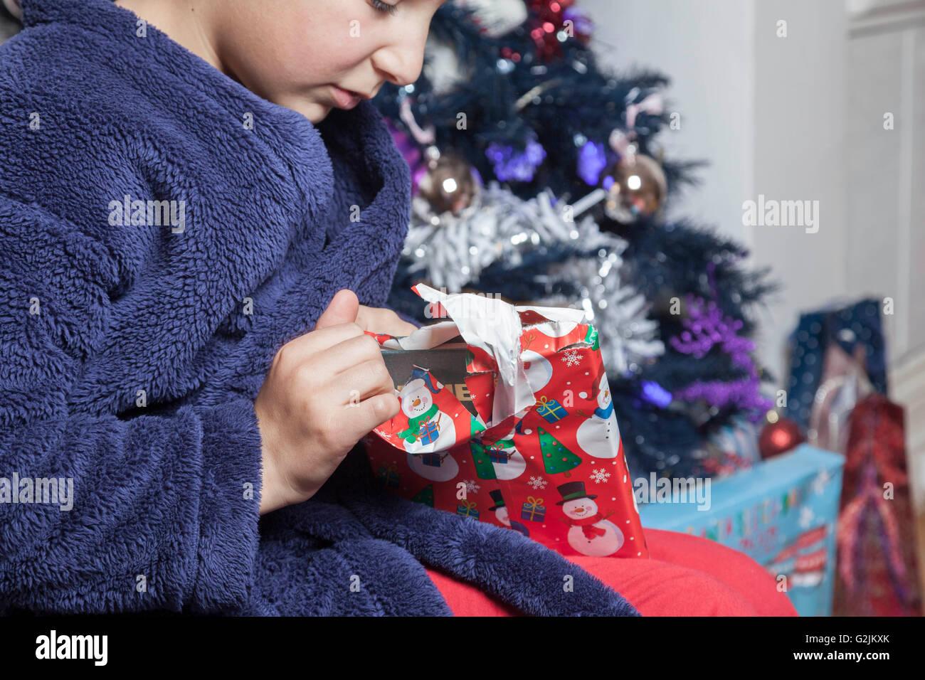 La mañana de Navidad- joven abre presente bajo el árbol de navidad - detalle Imagen De Stock