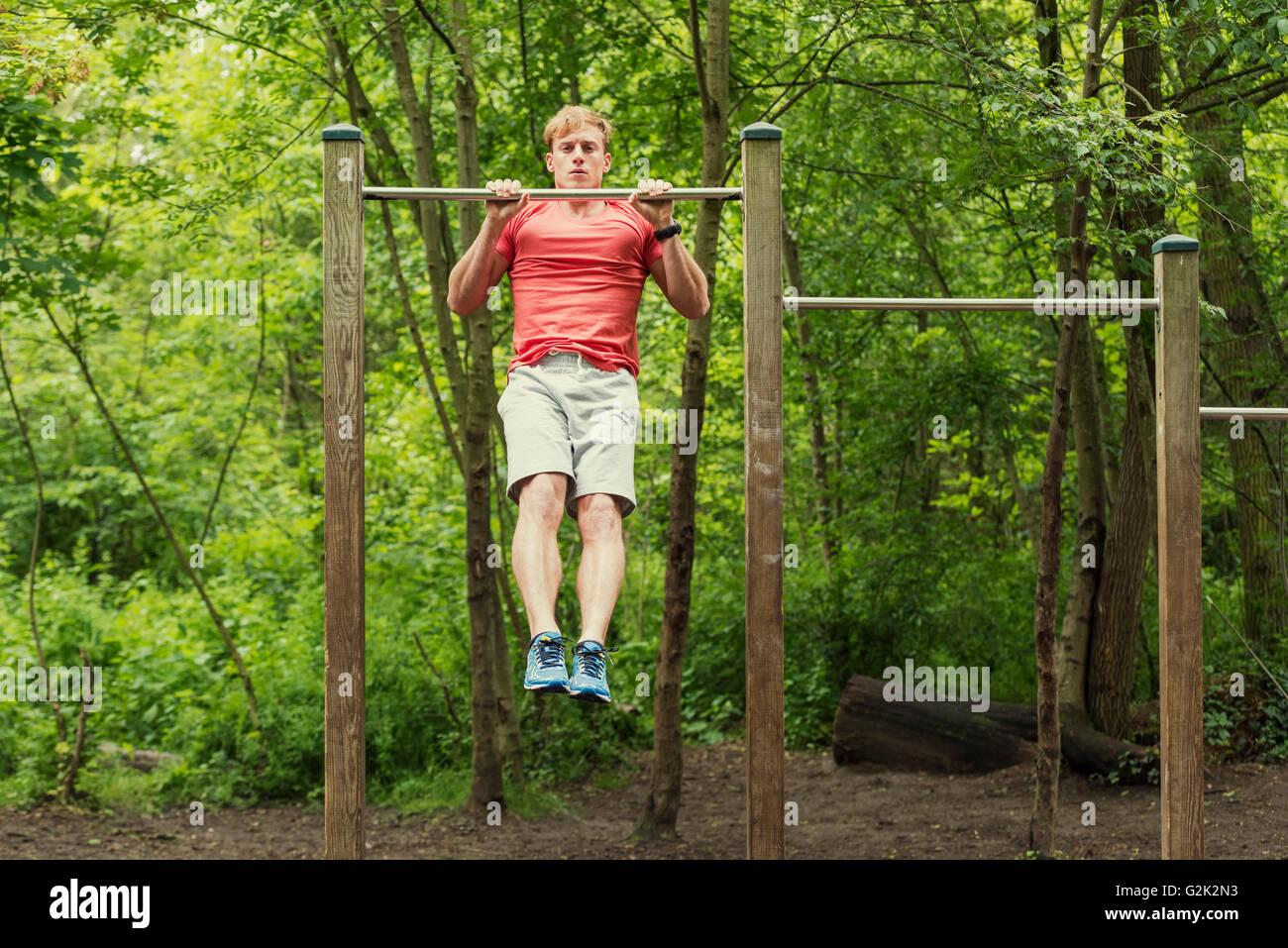 Atleta Masculino haciendo muscle-up en la barra horizontal Imagen De Stock