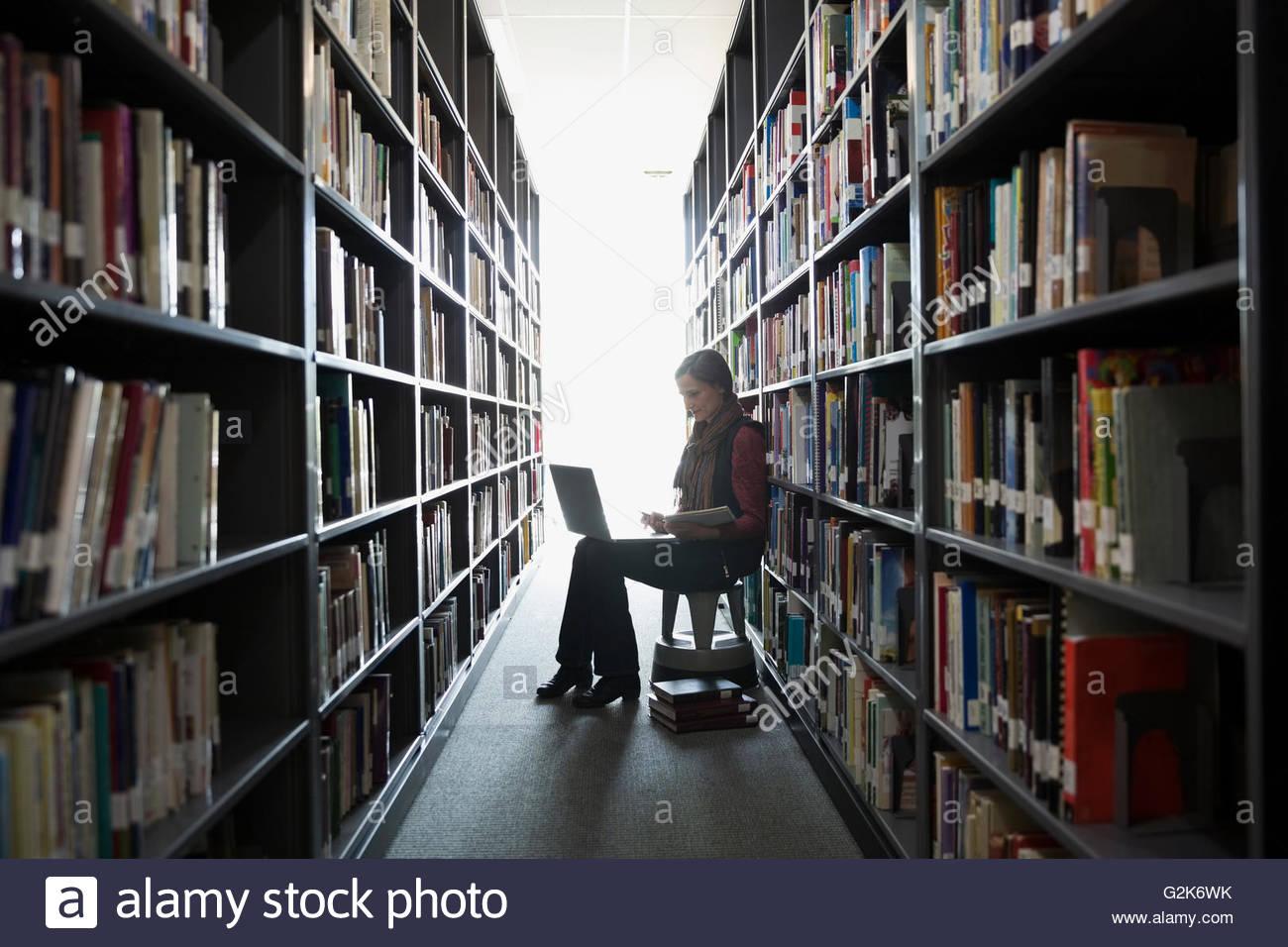 Educación de Adultos la investigación estudiantil en portátil entre estanterías de la biblioteca Imagen De Stock