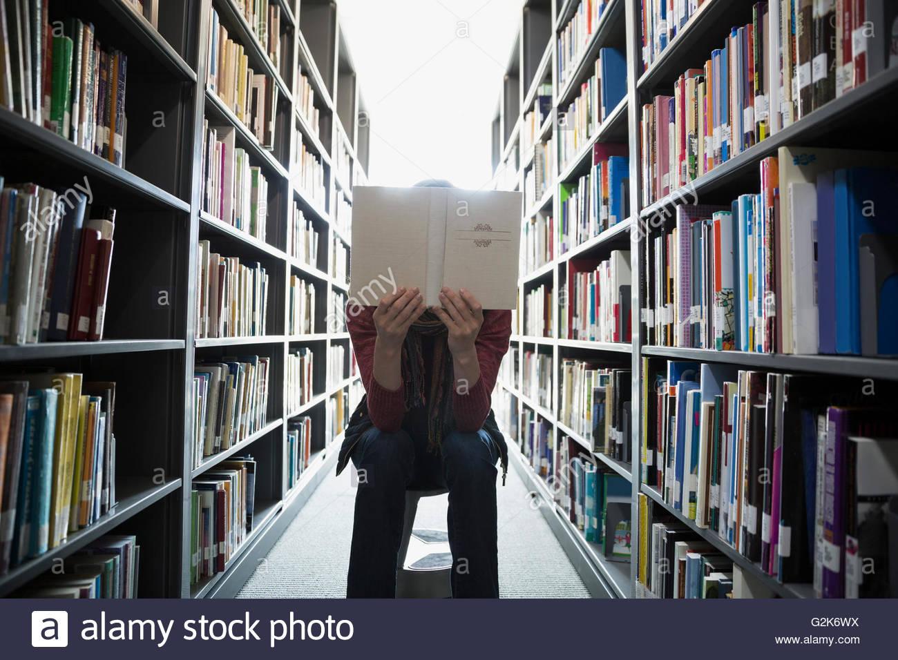 Estudiante de educación de adultos, leyendo entre estanterías de la biblioteca Imagen De Stock
