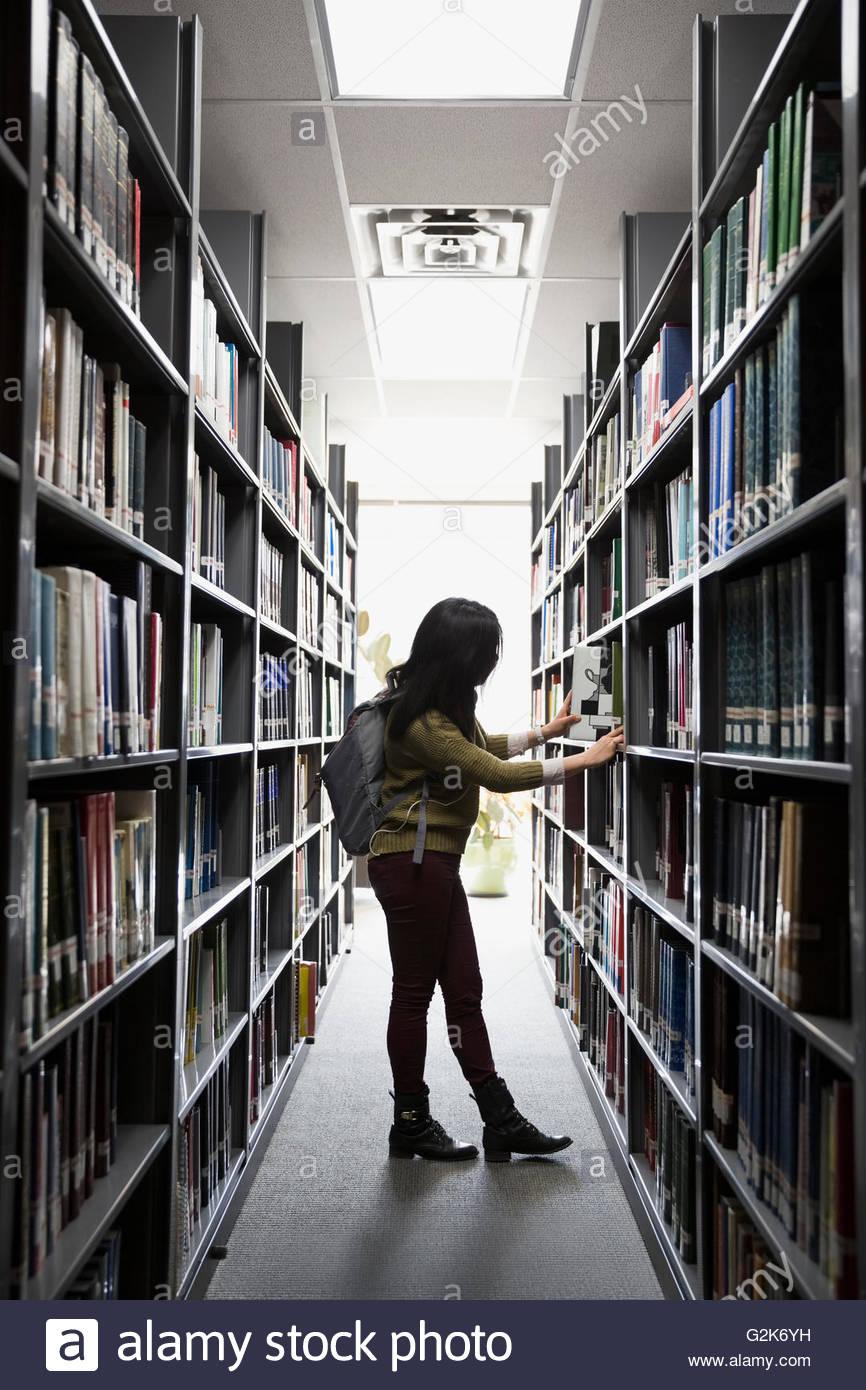 Estudiante universitario buscando libro en la biblioteca Imagen De Stock