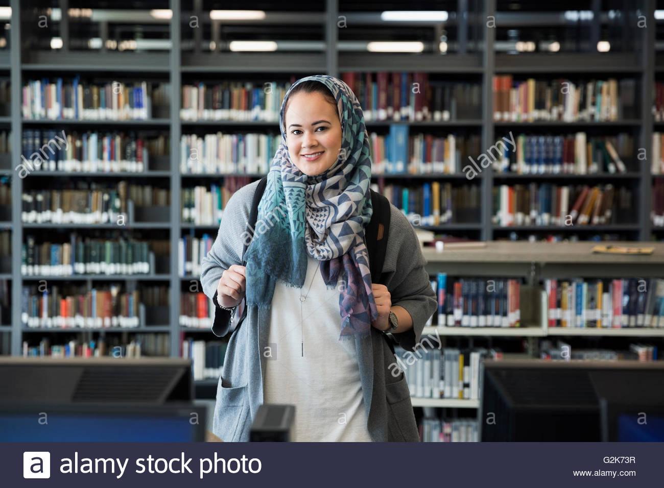 Retrato sonriente estudiante universitario vistiendo el hiyab en la biblioteca Imagen De Stock