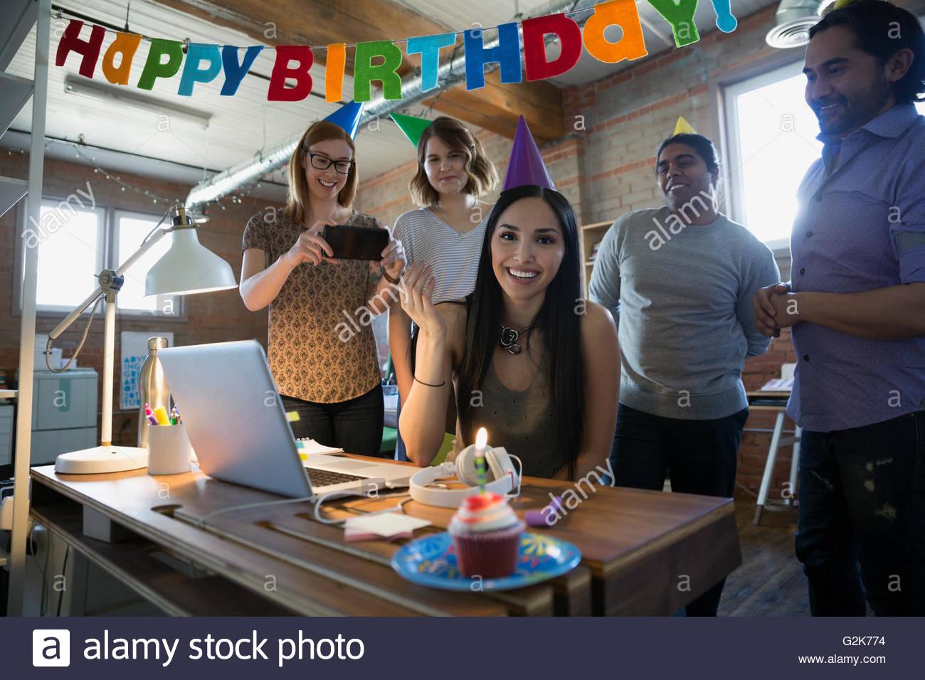 Retrato empresaria sonriente disfrutando de la fiesta de cumpleaños con los compañeros en la oficina Imagen De Stock
