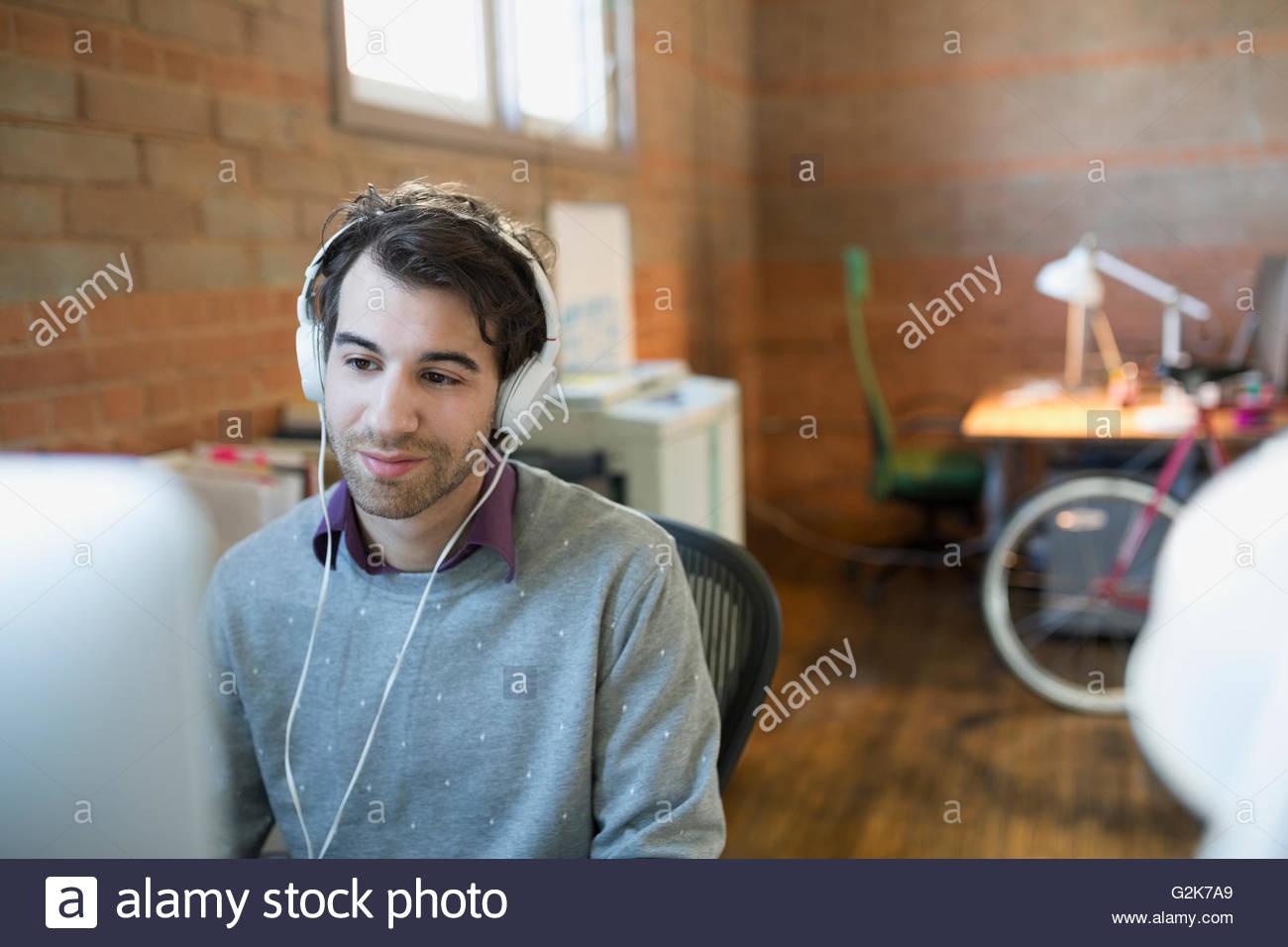 Diseñador con auriculares utilizando equipo de oficina Imagen De Stock