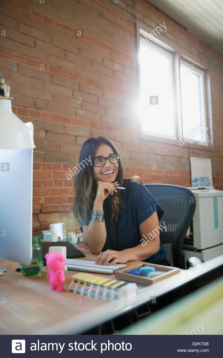 Sonriente empresaria creativa busca lejos en el equipo en Office Imagen De Stock