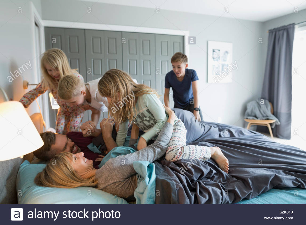 Los niños juguetones en pijama abordar en la cama de los padres Imagen De Stock