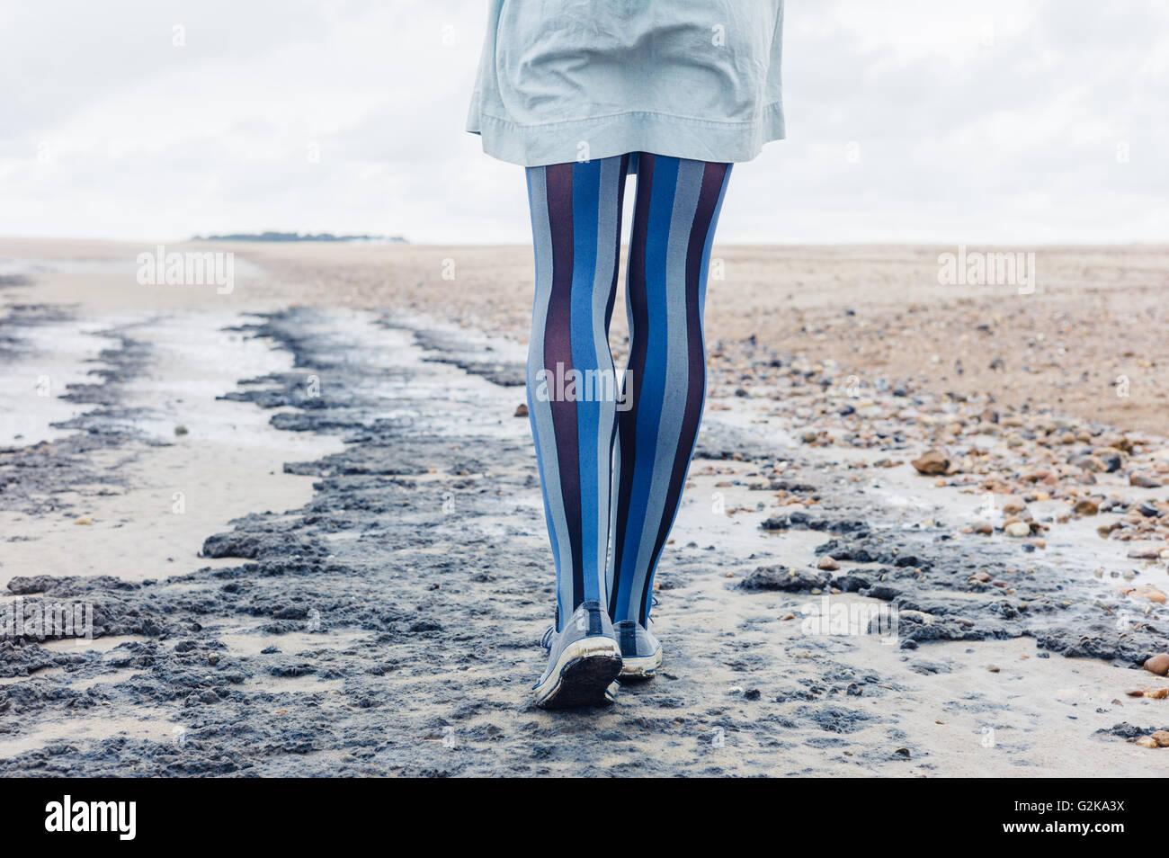 Las piernas de una mujer joven como ella está caminando en la playa Imagen De Stock