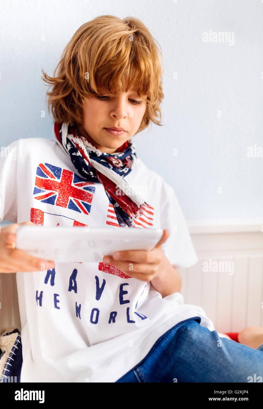 Retrato de niño fresco en casa mediante tableta digital Imagen De Stock
