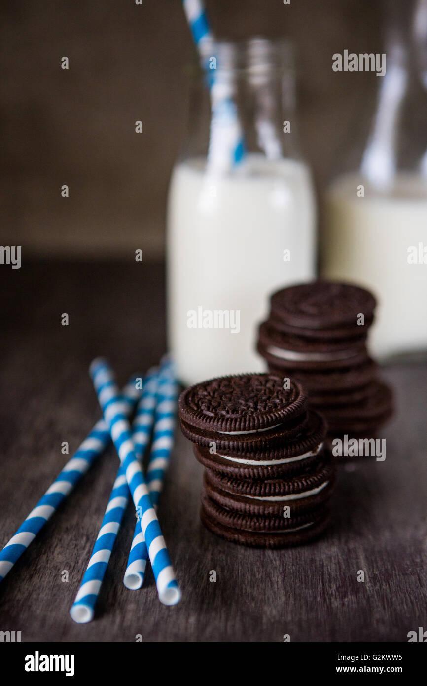 Dos pilas de OREO cookies con pajitas rayas y dos botellas de leche Imagen De Stock