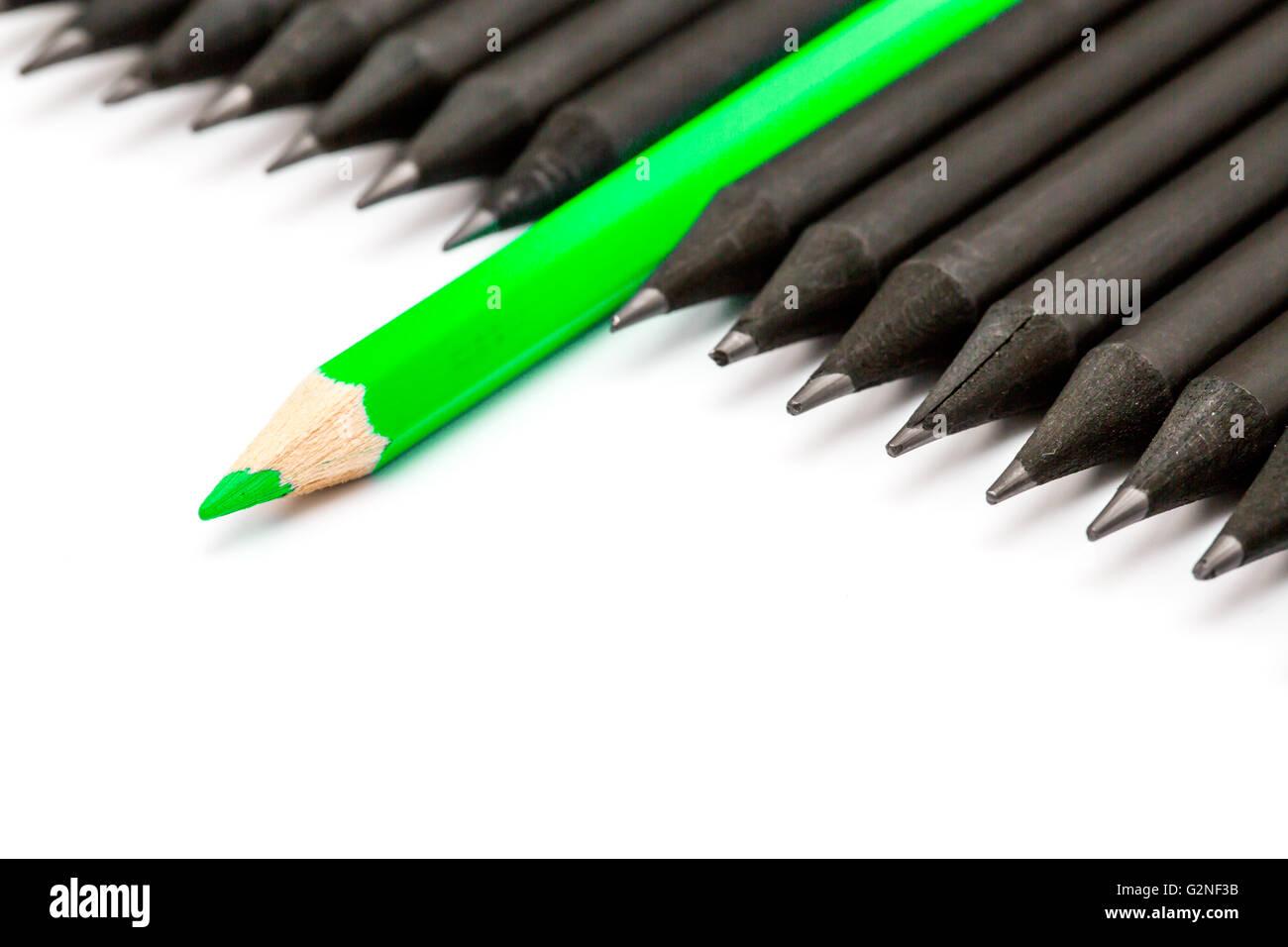 Lápiz verde que sobresalían desde la fila de lápices de color negro. Imagen De Stock