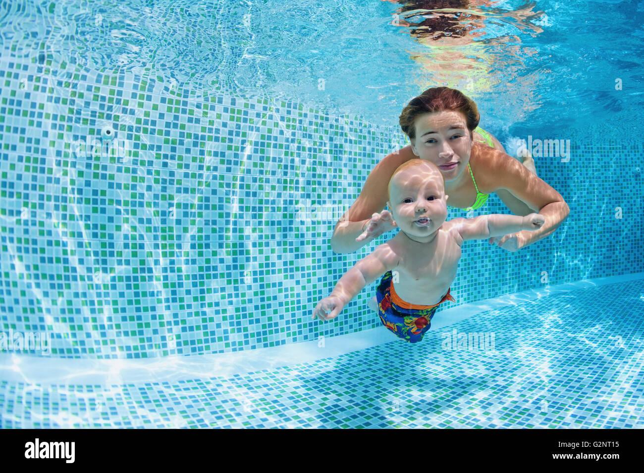 Lección de natación infantil - Bebe con la madre, aprender a nadar, bucear bajo el agua en la piscina. Imagen De Stock