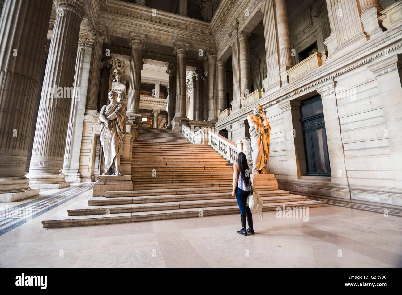 Una mujer joven con su mochila, mirando hacia las escaleras en frente de ella en el lado derecho de la entrada al Imagen De Stock
