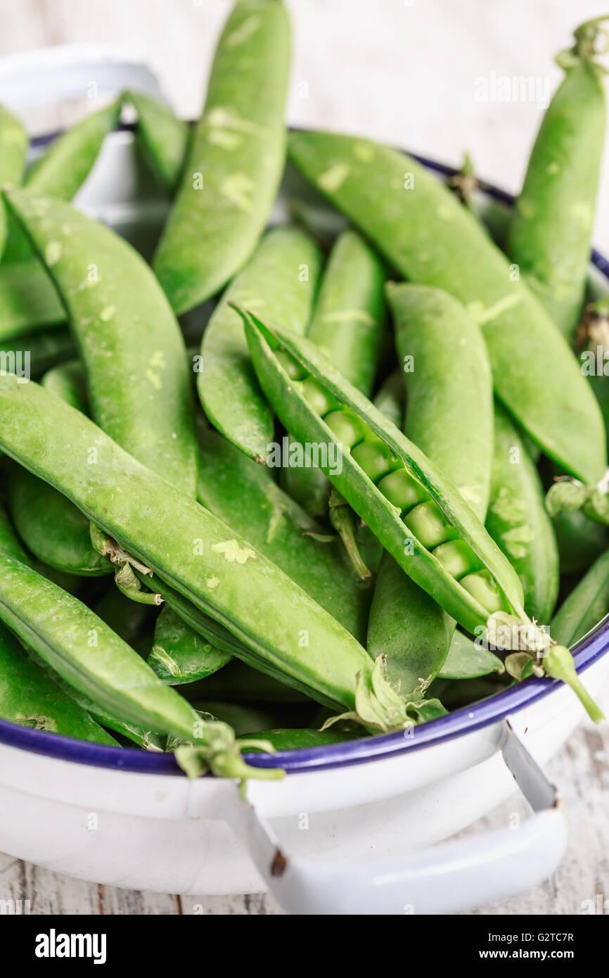 Las vainas de arvejas frescas verde en un tazón Imagen De Stock