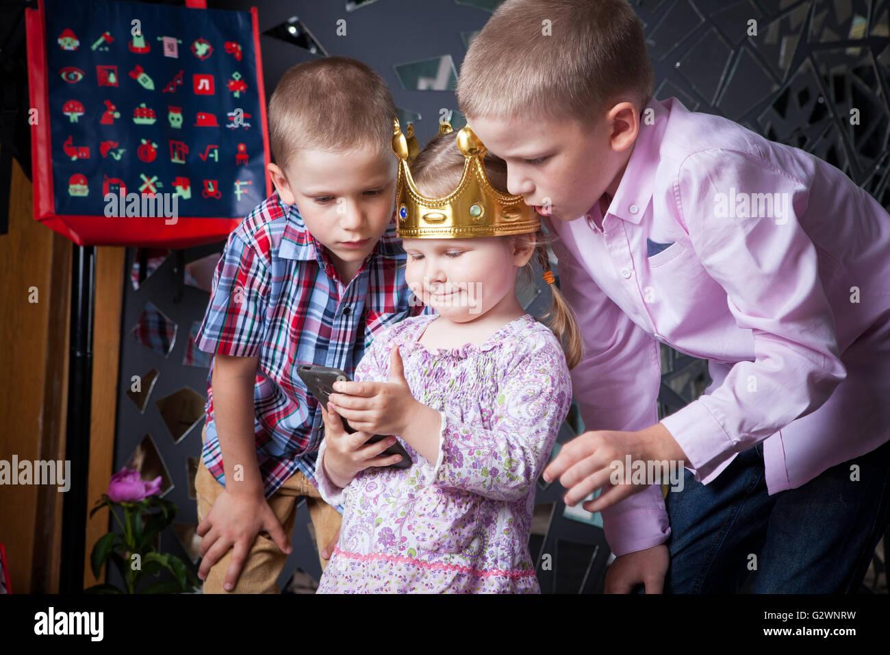 Los niños y niñas de teléfono inteligente considerar cuidadosamente el teléfono inteligente, la chica con los muchachos, Foto de stock