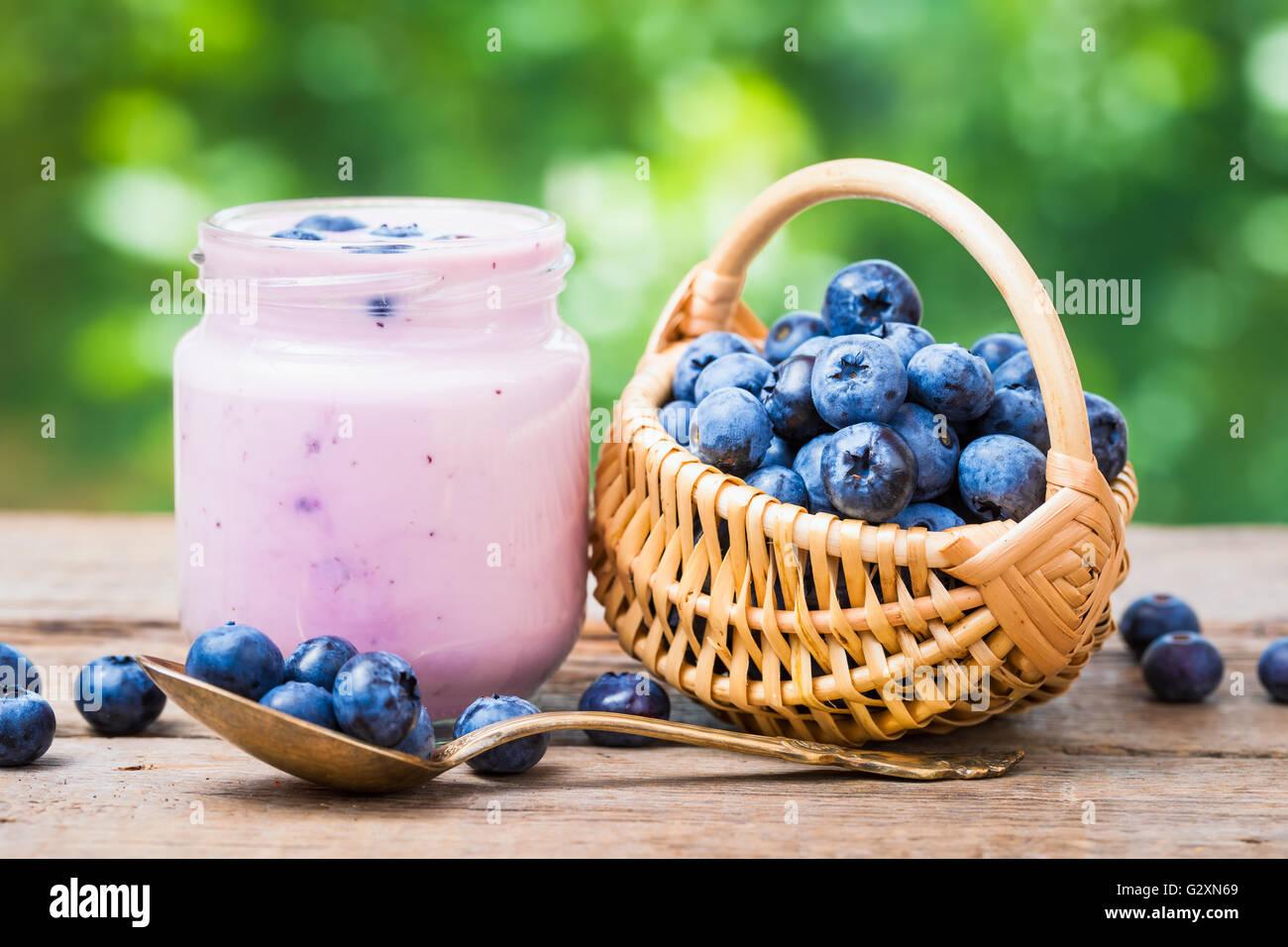 Arándanos frescos en tarro de yogur y una cestita de arándanos. Imagen De Stock