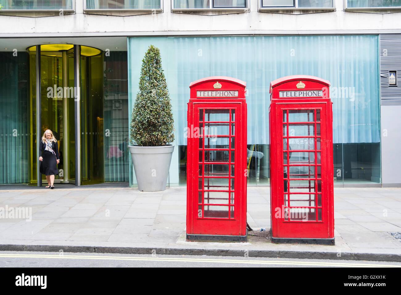 Una mujer emerge de una puerta de oficina detrás de dos kioscos telefónicos de Londres Giles Gilbert Scott K6, de grado II, de color rojo brillante, Londres, Reino Unido Foto de stock