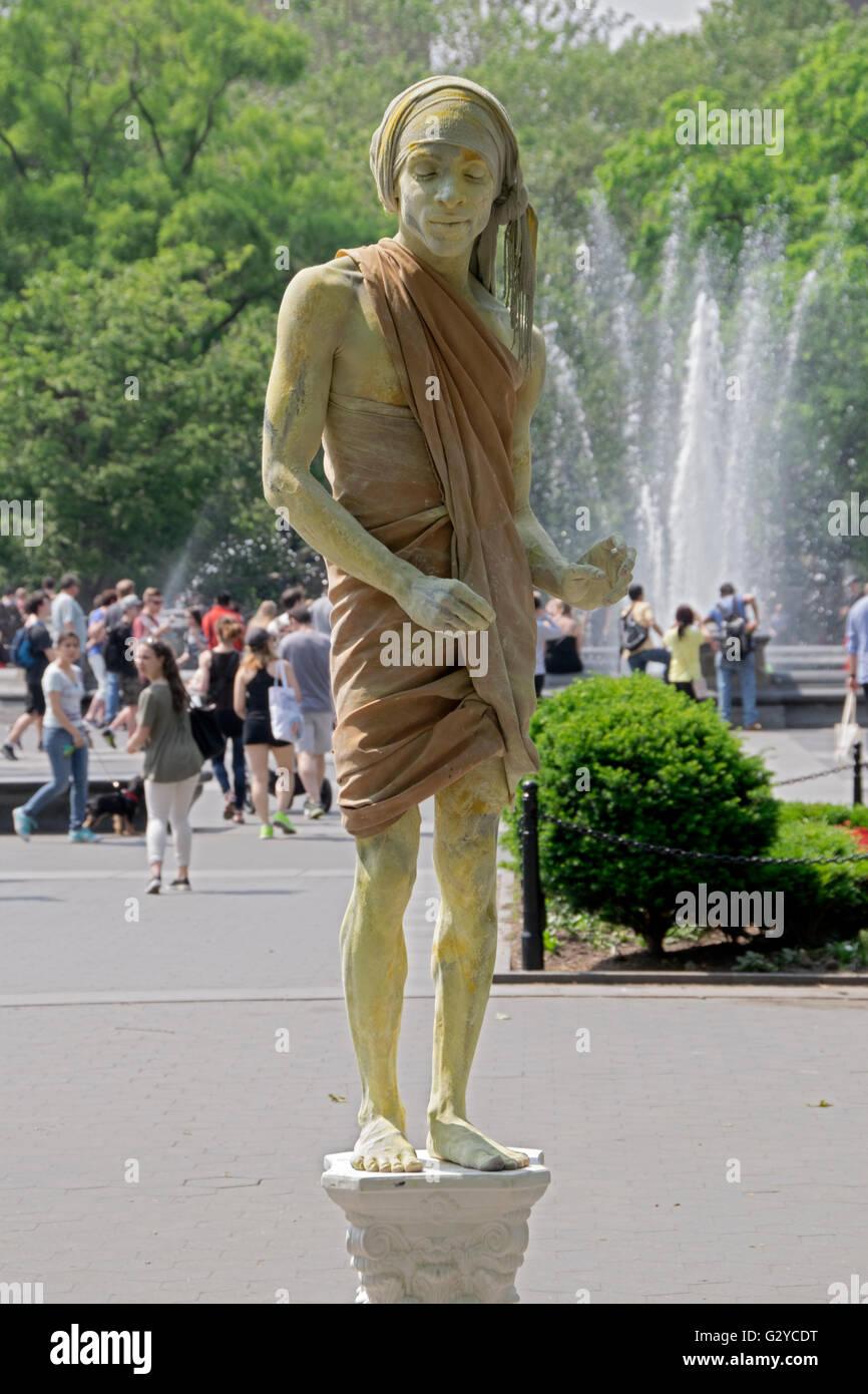 Un músico callejero mime que permanece inmóvil para recaudar donaciones en el parque Washington Square en Greenwich Foto de stock