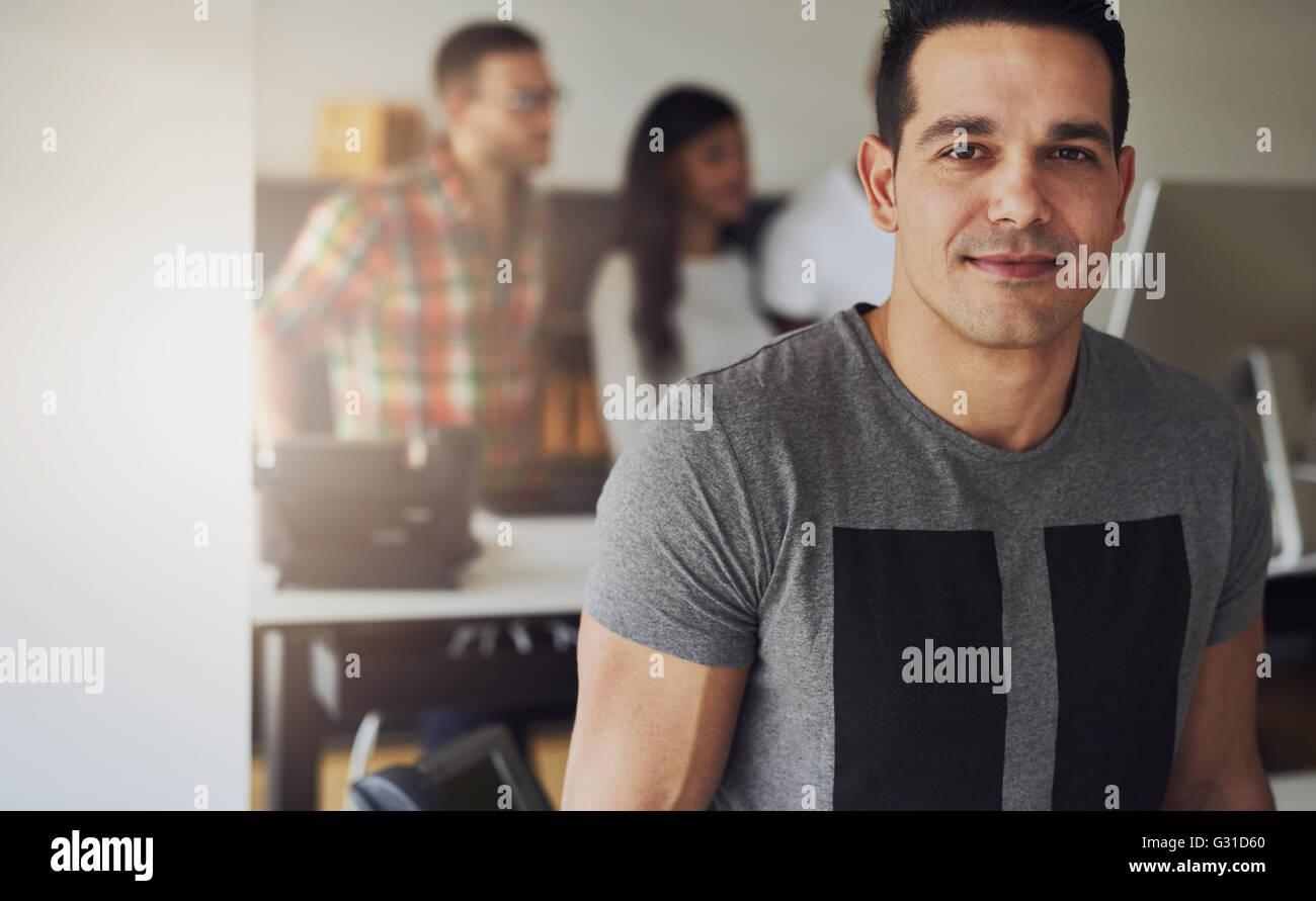 Cerca del hermoso macho trabajador vistiendo la camiseta de manga corta de color gris en la pequeña oficina Imagen De Stock