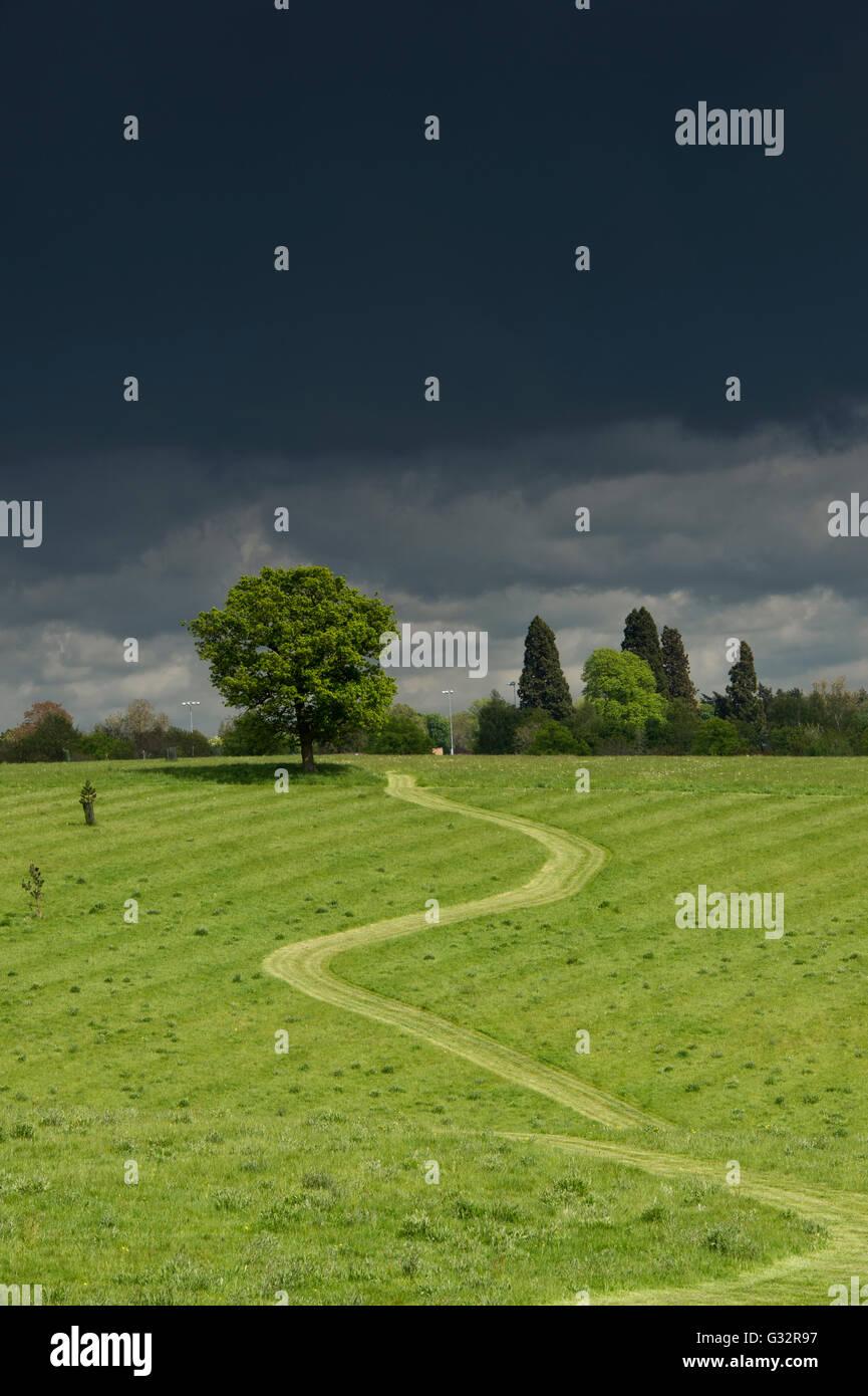 Sendero iluminado contra un cielo tormentoso oscuro a través de un campo de Oxfordshire. Banbury, Oxfordshire, Imagen De Stock