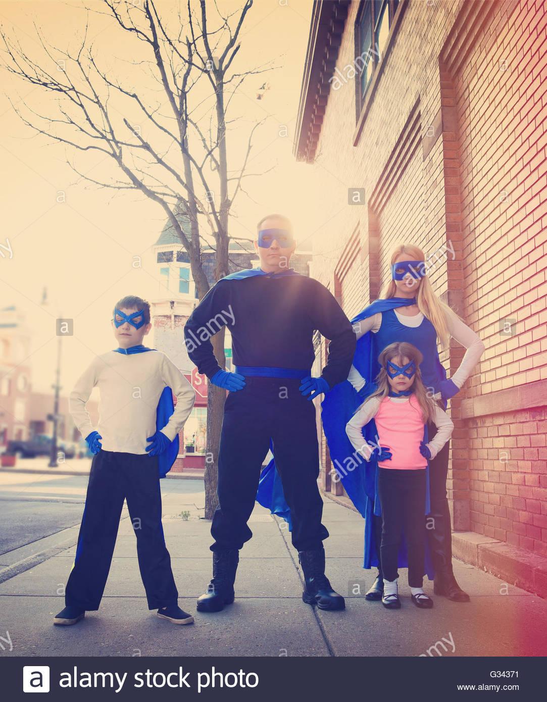 Una joven familia super hero están de pie afuera con azul capes y máscaras de protección, la fuerza Imagen De Stock