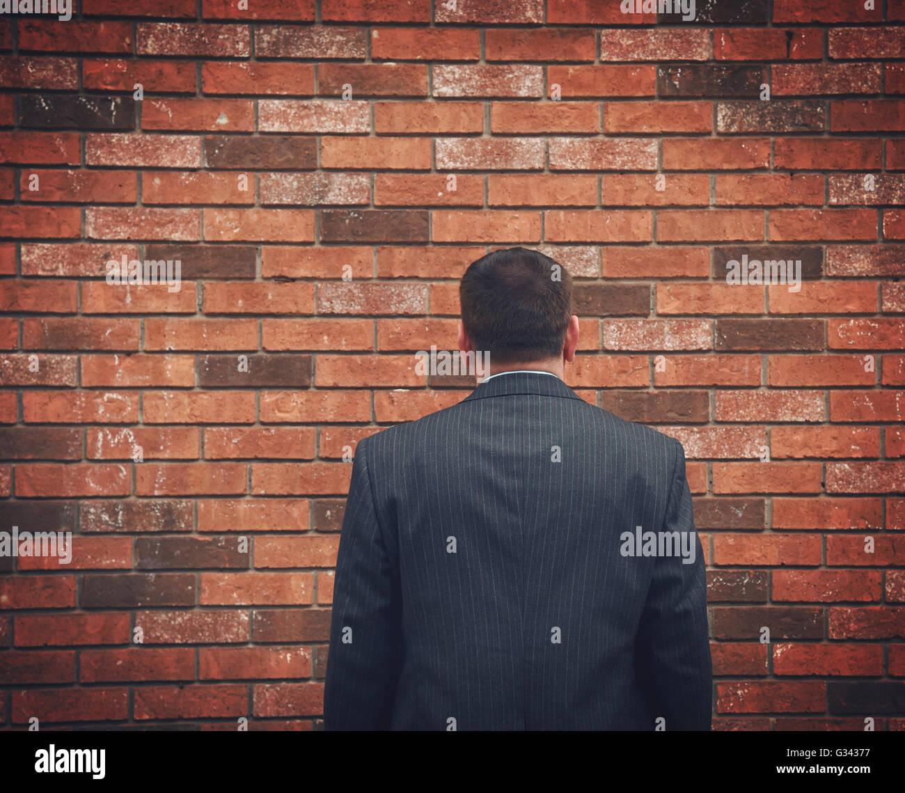 Un hombre de negocios ha de espaldas y mirando a una pared de ladrillo. Puede representar un obstáculo, tristeza Imagen De Stock