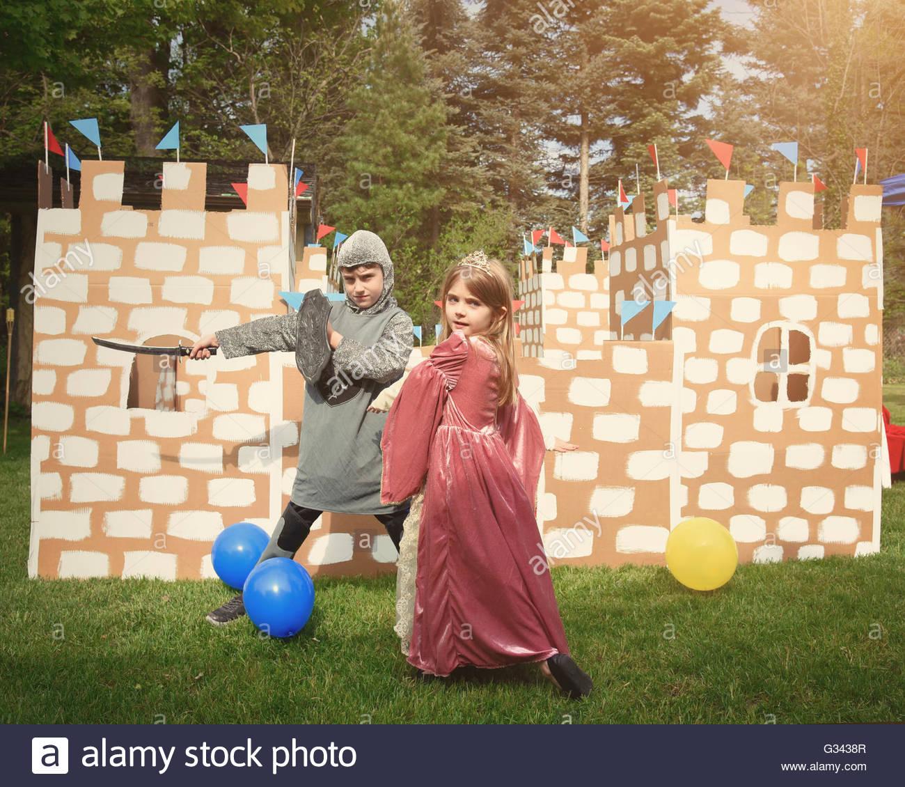 Los niños se visten con trajes de caballero y princesa en frente de un castillo de cartón caseros fuera Imagen De Stock