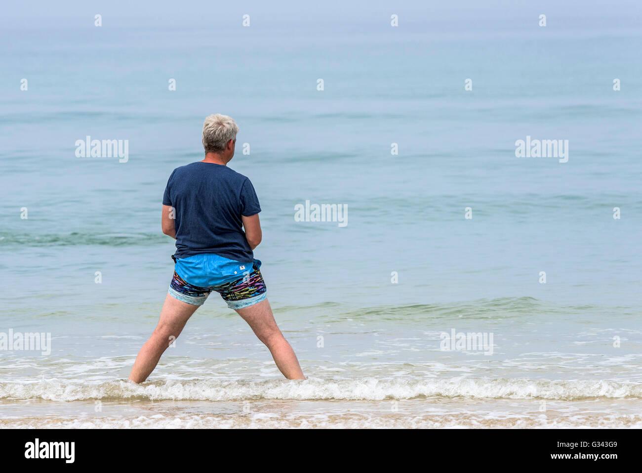 Un hombre con una extraña postura en Fistral Beach en Newquay, Cornwall. Imagen De Stock