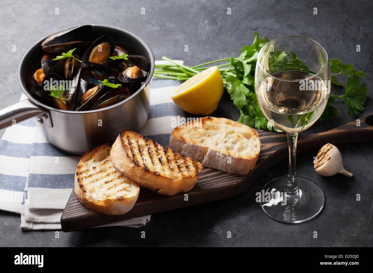 Mejillones en olla de cobre, tostadas de pan y de vino blanco sobre la mesa de piedra. Centrarse en la copa de vino Foto de stock