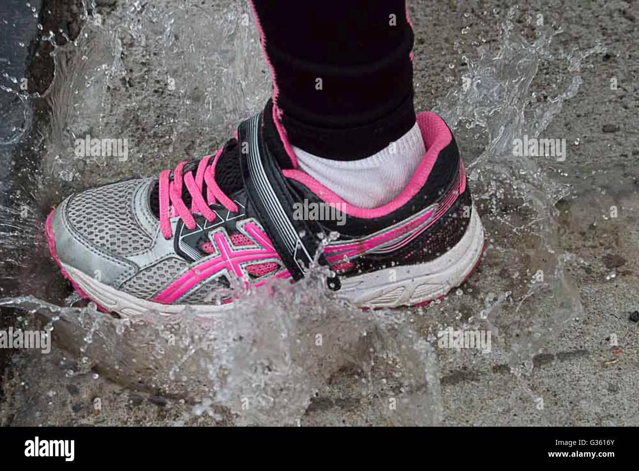 Calzado deportivo, zapatos, zapatillas de deporte, zapatos, corriendo a través de un charco Imagen De Stock