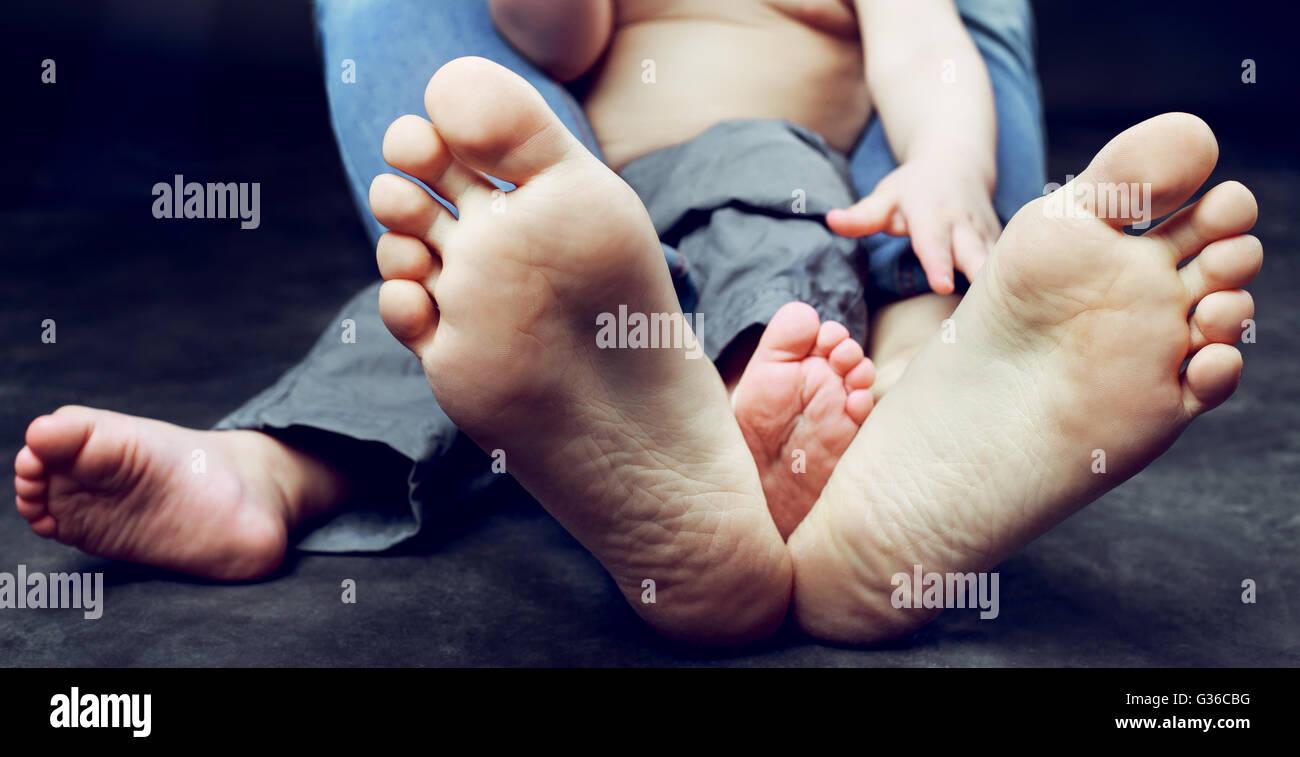 Los pies de una joven madre y su bebé, con jeans y sentada en el suelo Foto de stock