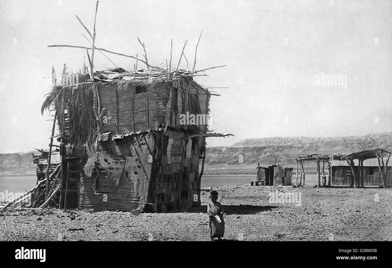 Una choza rudimentaria construida por un árabe fellah (campesino, agricultor o trabajador agrícola), por el Mar Muerto, Tierra Santa. Está hecho de palos, esteras y latas de aceite. Fecha: 1920 Foto de stock