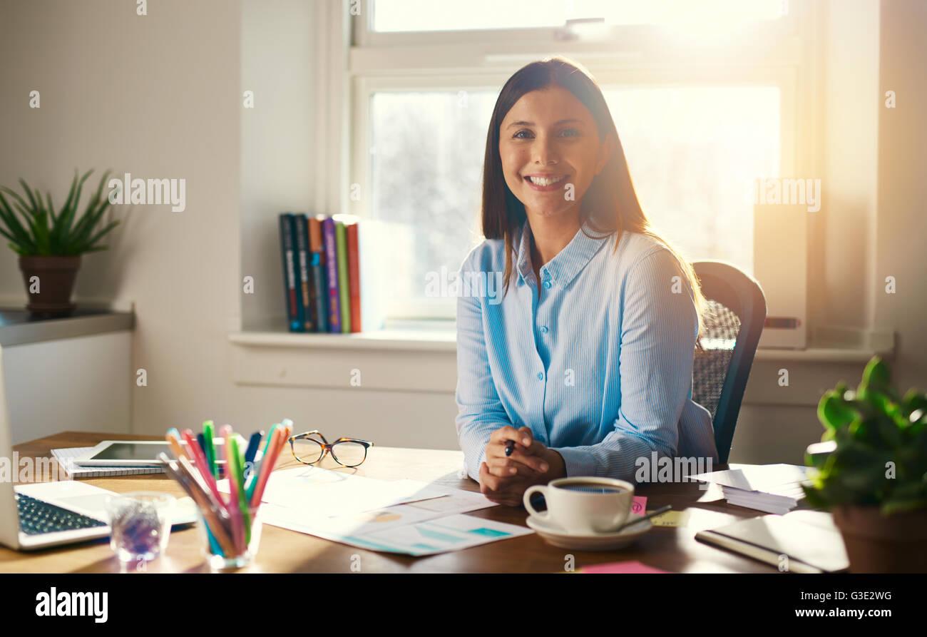 Seguros de mujer de negocios sentada en la mesa con las manos cruzadas sonríe a la cámara Imagen De Stock