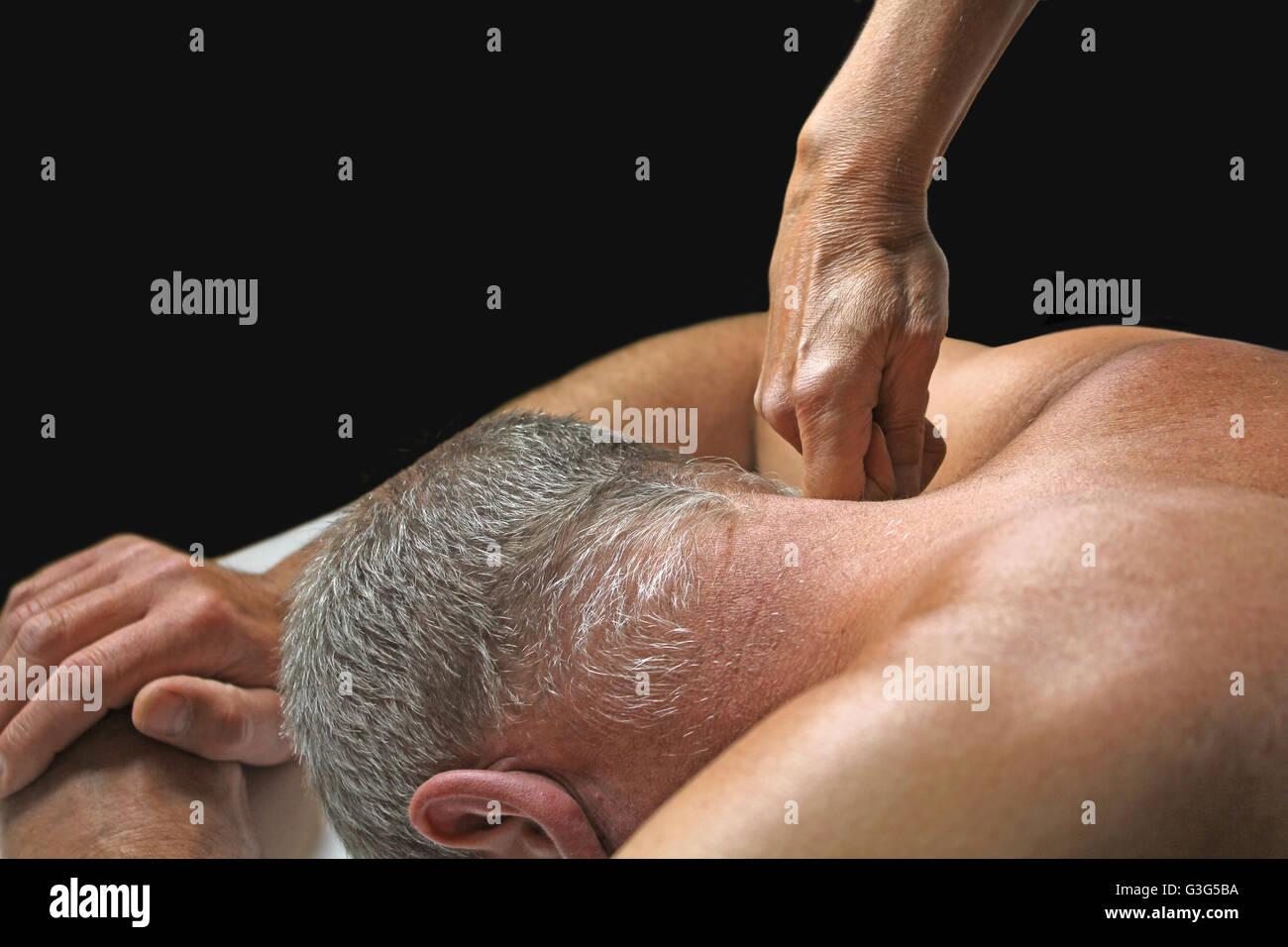 Terapeuta aplica presión al cuello del cliente propensas masculino sobre un fondo negro con espacio de copia Imagen De Stock