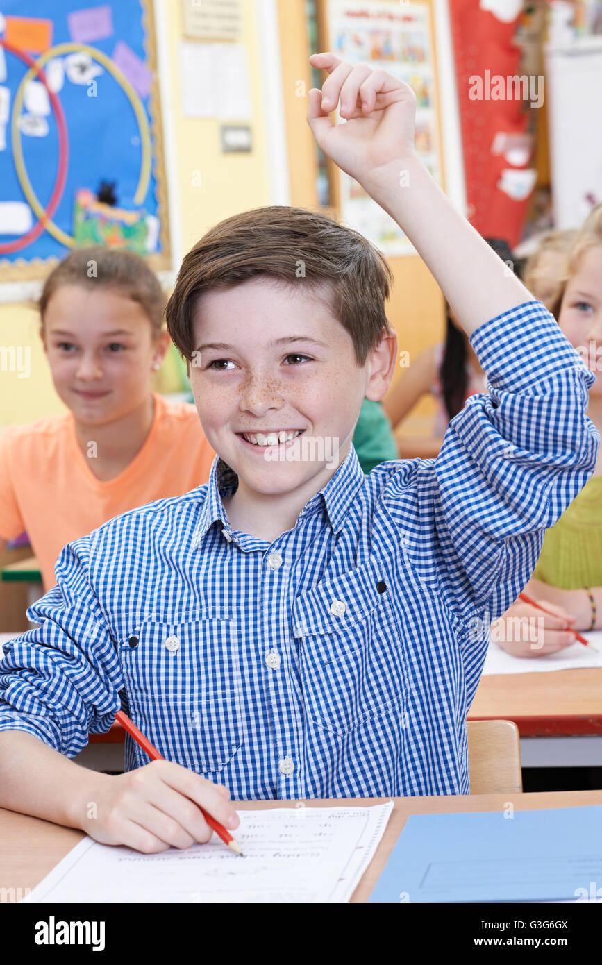 Estudiante varón levantando la mano para responder a la pregunta sobre la clase Imagen De Stock