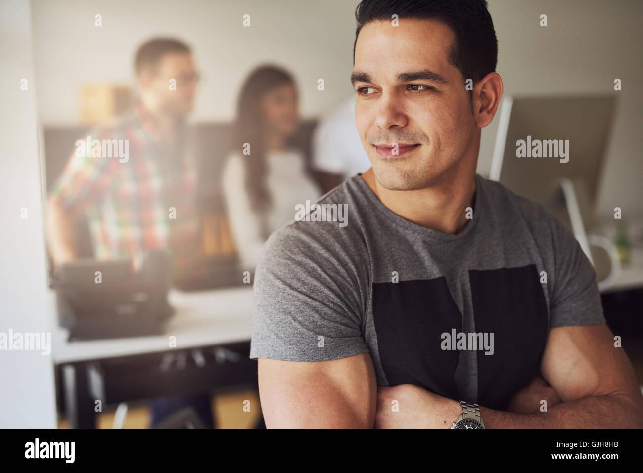 Cerca de calma hermoso macho trabajador con armas muscular plegada vistiendo la camiseta de manga corta de color Imagen De Stock