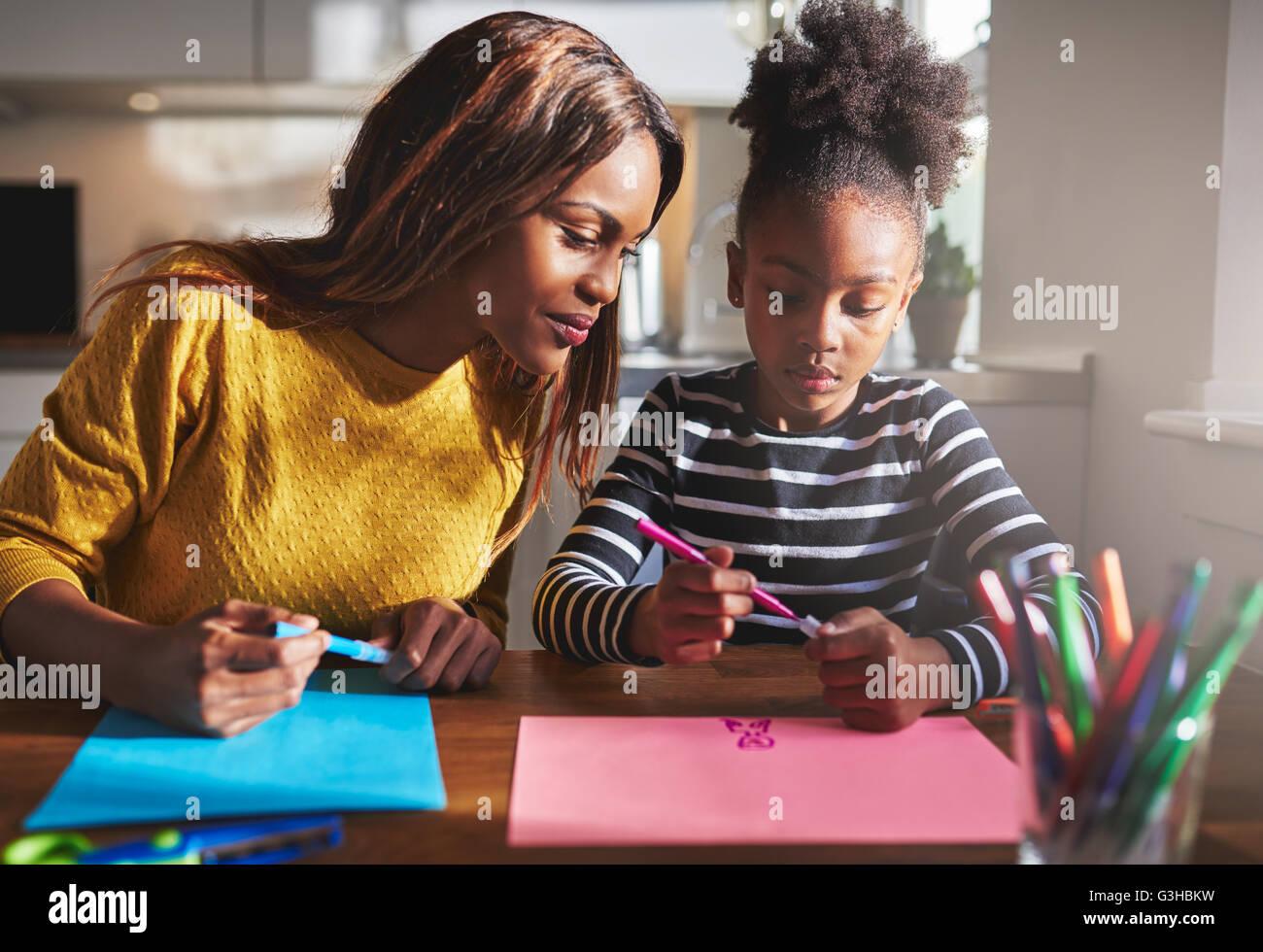 La mamá y el niño dibuja en la cocina, madre e hija negra Imagen De Stock