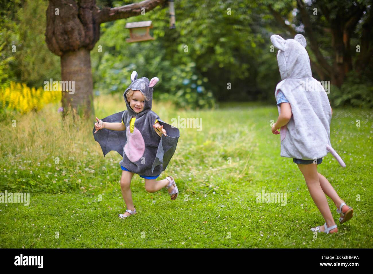 Dos hermanas jóvenes vestidos de traje de ratón corriendo en el jardín Foto de stock