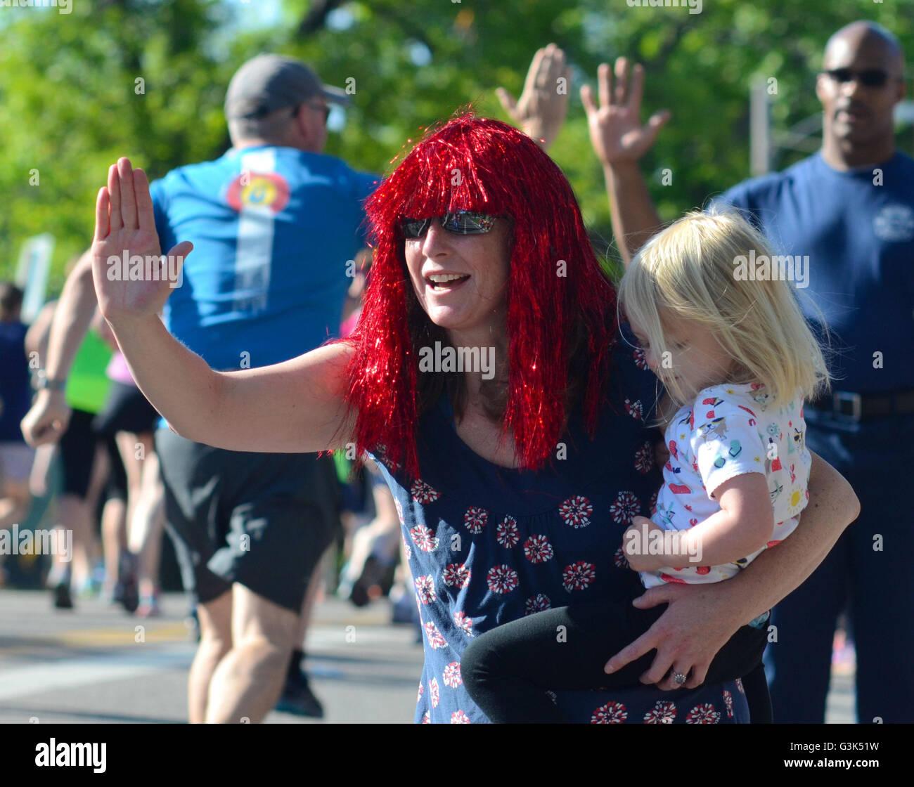 Mujer con peluca roja y niño aliente a los participantes en el Boulder Bolder 10k Día Memorial Race en Imagen De Stock