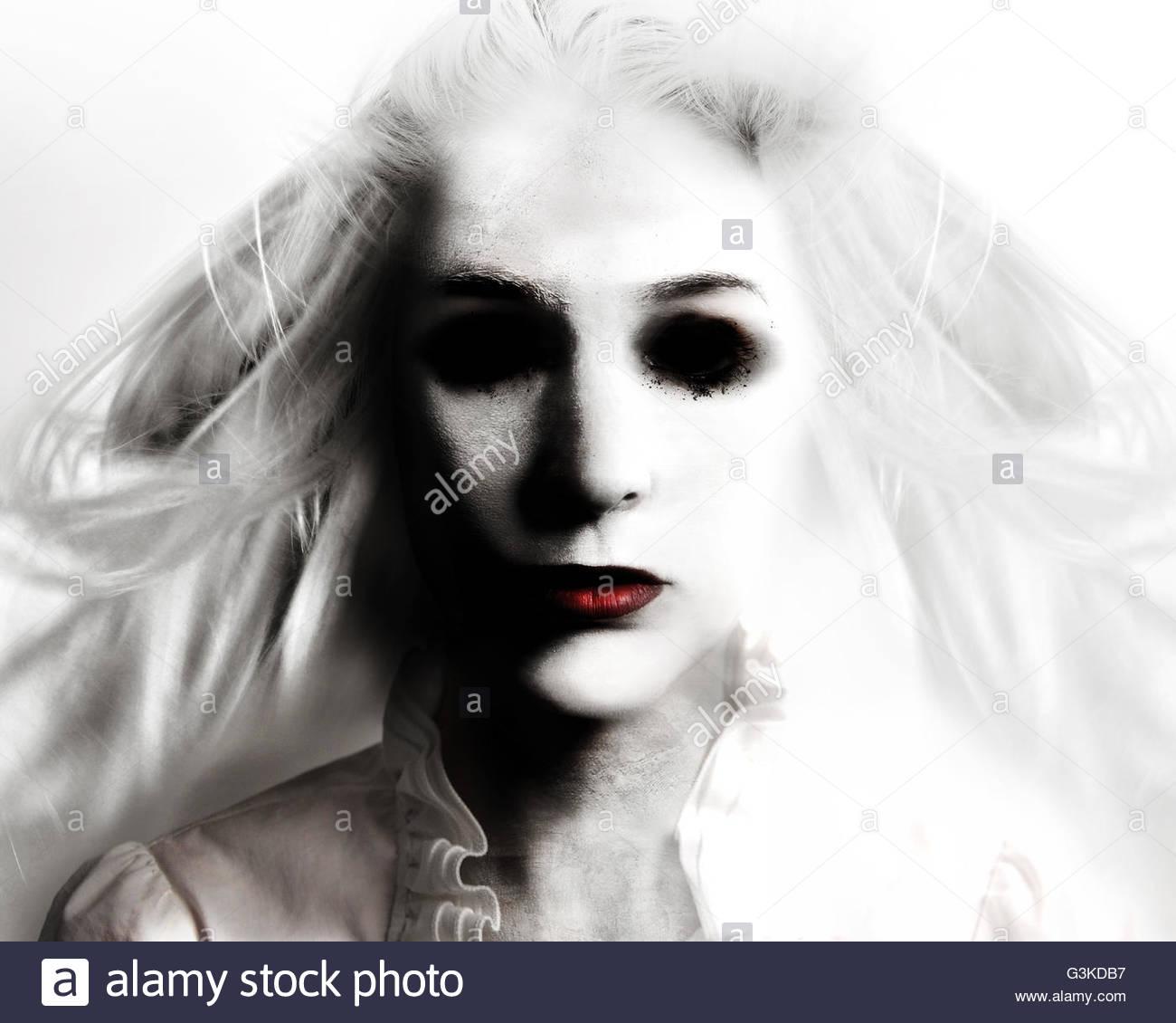 Un miedo mujer malvada con ojos negros y labios rojos es la muerte sobre un fondo blanco para un temor o concepto Imagen De Stock