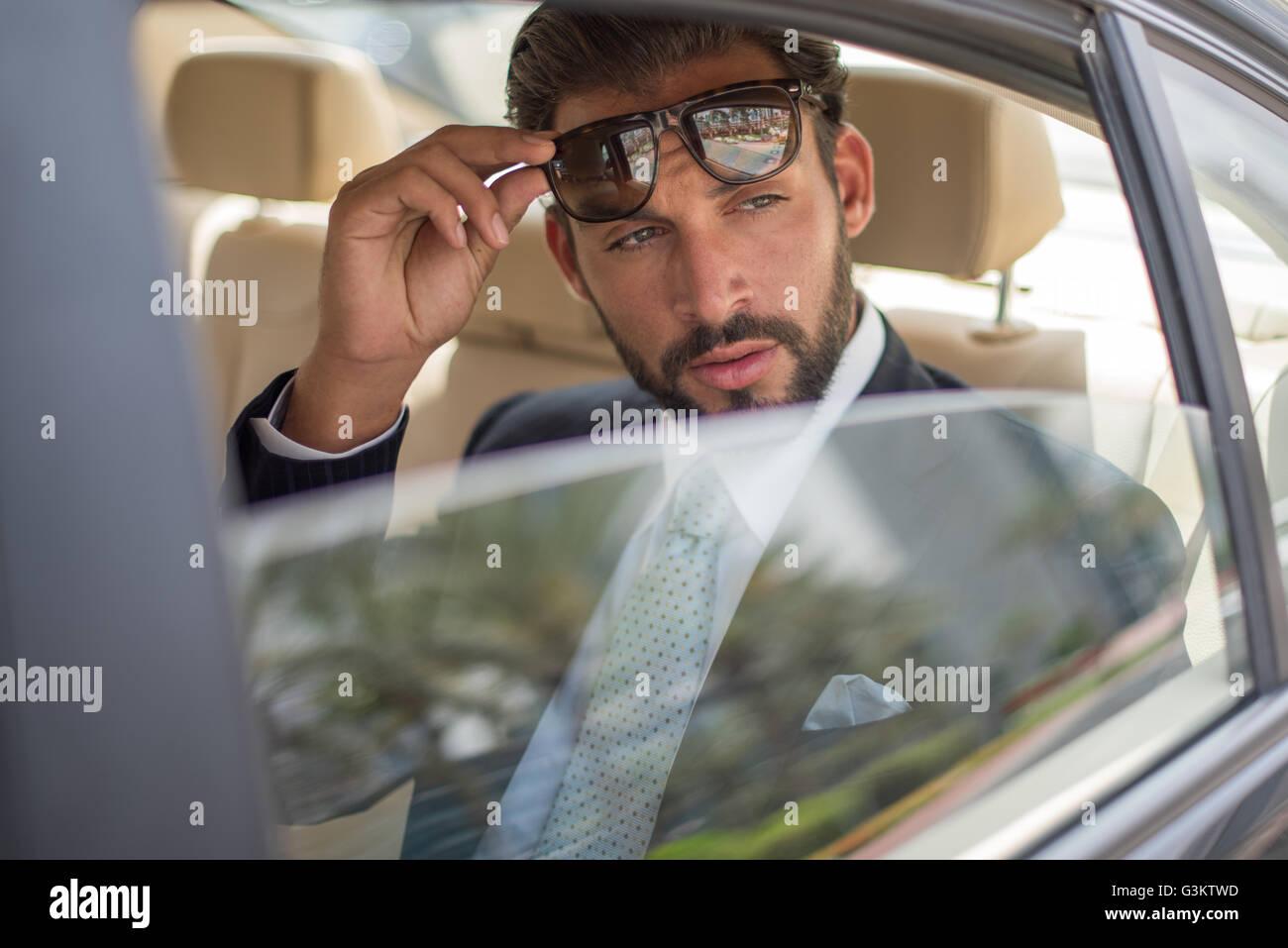 446a4f2992 Joven empresario sosteniendo gafas de sol en coche backseat, Dubai,  Emiratos Árabes Unidos.