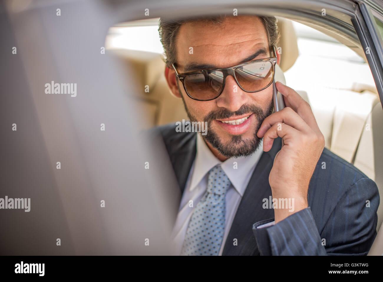 d4abb7a4e4 Empresario joven con gafas de sol hablando sobre smartphone en coche  backseat, Dubai, Emiratos Árabes Unidos.