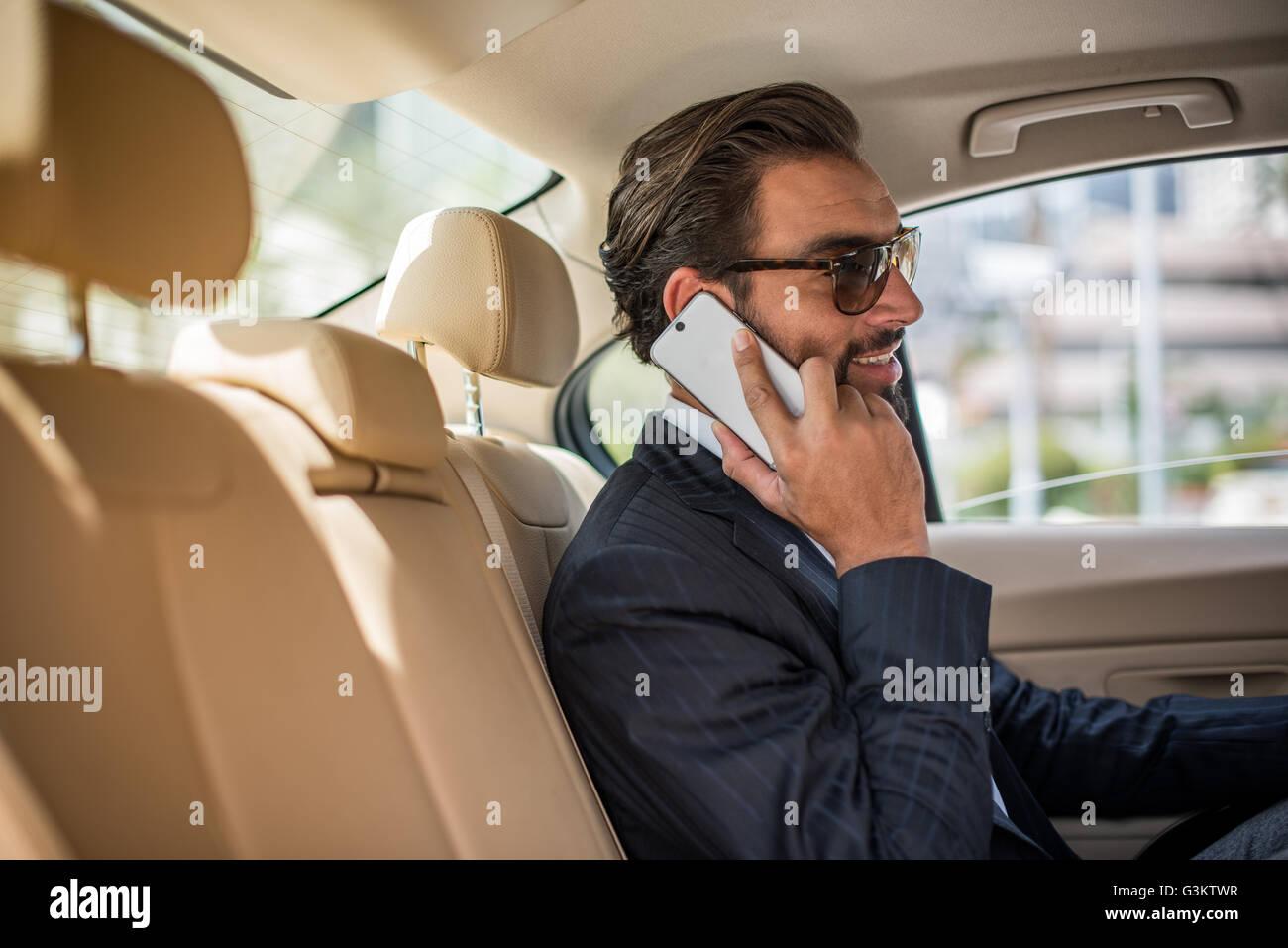 4265568683 Joven empresario en coche backseat con gafas de sol y hablando en smartphone,  Dubai, Emiratos Árabes Unidos.