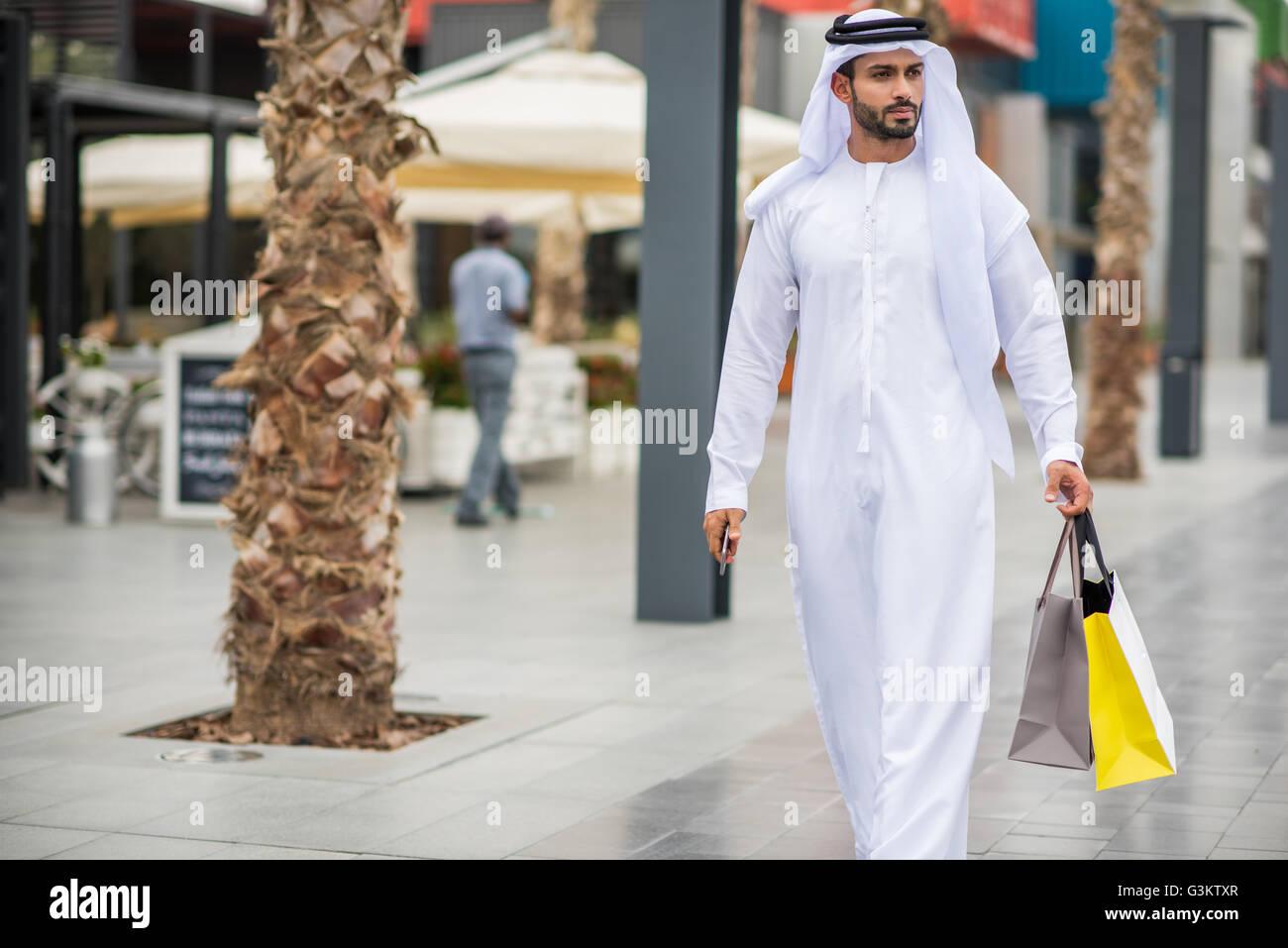 7b32703bd6b61 Hombre vestido con ropa tradicional de Oriente Medio caminando por la calle  llevando bolsas de compras, Dubai, Emiratos Árabes Unidos.