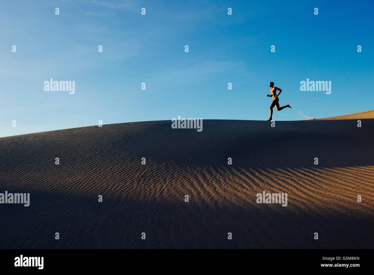 Mujer desnuda en el desierto ejecutando en dune Foto de stock