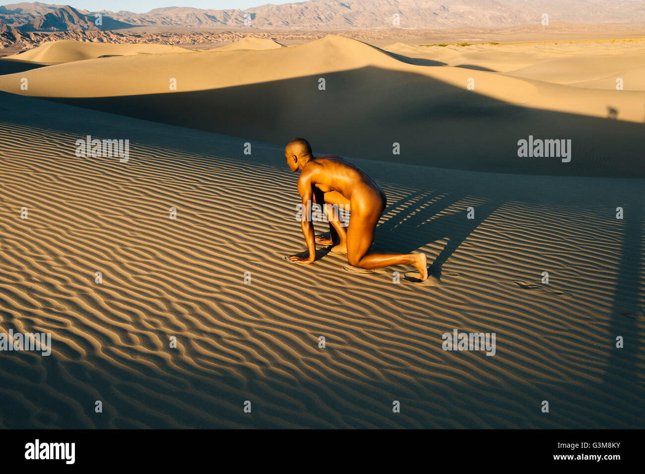 Mujer desnuda en la posición de arranque en el postre Foto de stock