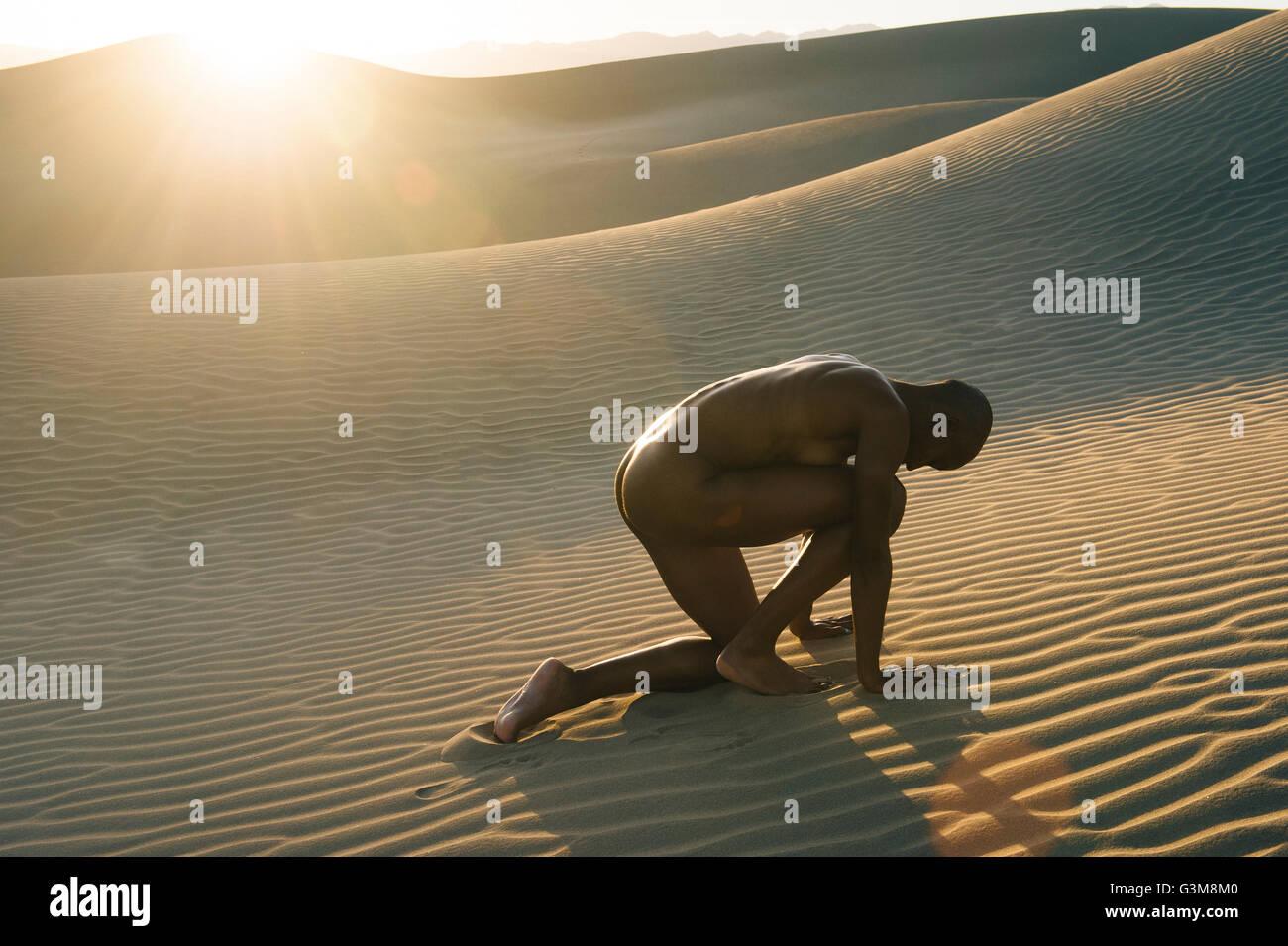 Mujer desnuda agazapado en el desierto Foto de stock